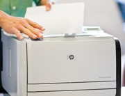 Close up of man pulling documents out of HP LaserJet