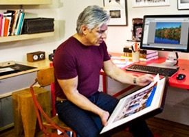 Man framing a photo in his home office