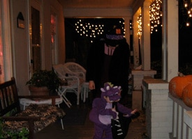 Trick-or-treaters on a dark porch