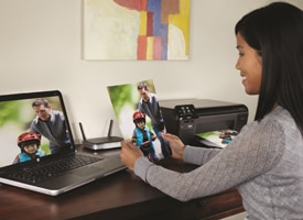 woman admiring photo with HP All-in-One in background