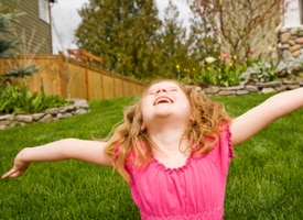 Photo of girl spinning and smiling on lawn