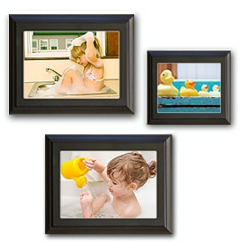 Three photos in black frames, displayed on a wall