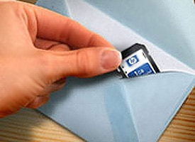 A hand slipping a memory card into an envelope