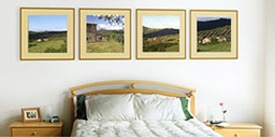 Picture of framed photos hanging above bed
