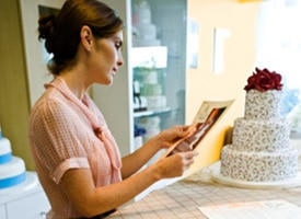 Caterer with cake, examining photos