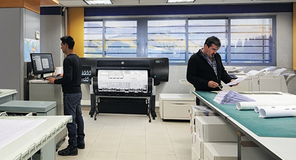 Man looking at computer, other man reviewing documents and  DesignJet printer on the background