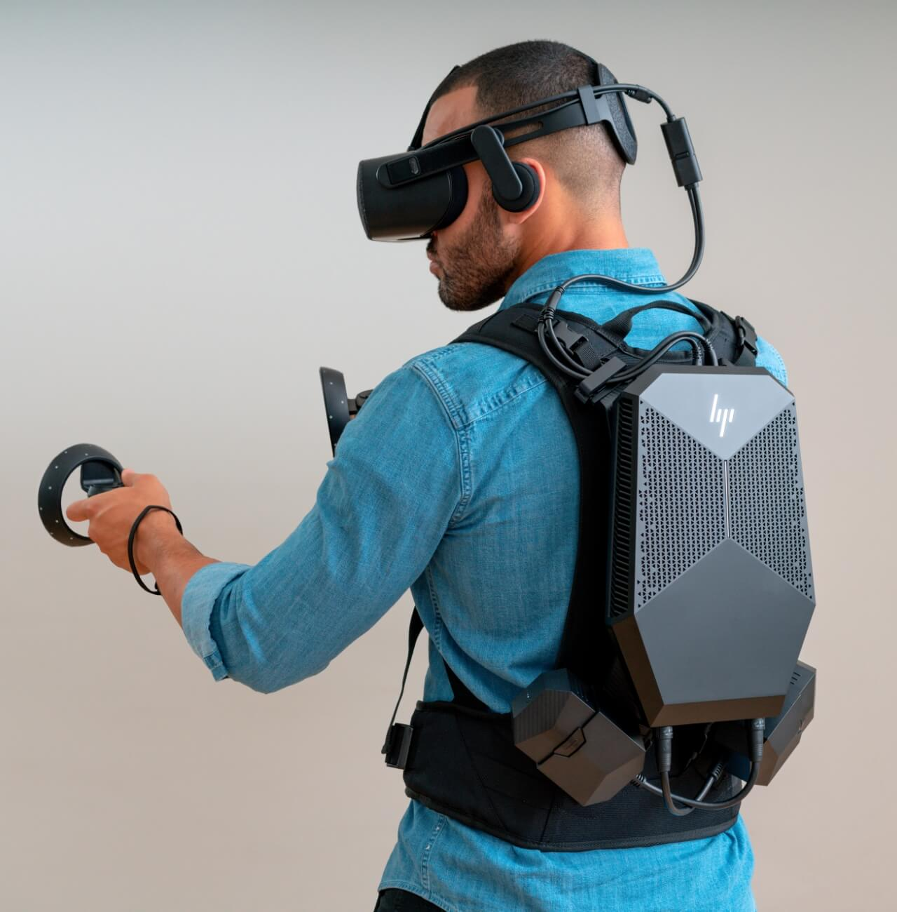 Man wearing VR Backpack, headset and hand controls