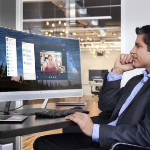 man is video conferencing with laptop docking with large curved business monitor