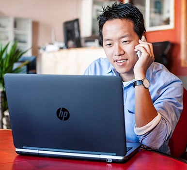 Man on the phone using an HP computer