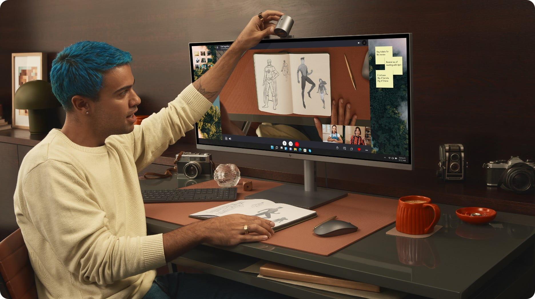 A man is adjusting a camera that is placed at the top of an HP ENVY 34-inch All-in-One Desktop