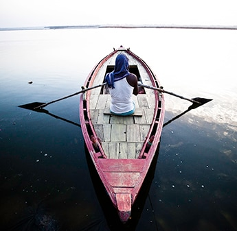 rear view of a man sailing on a boat in a lake