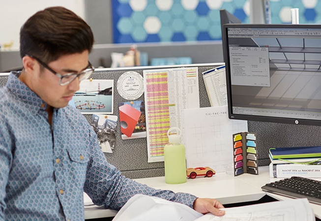 Man reviewing print next to HP monitor