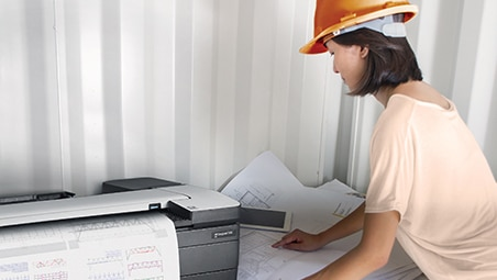 Construction worker in hard hat printing floor plans on HP DesignJet at job site