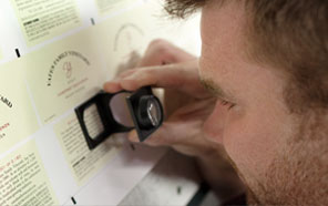 a man checking printed typography with a magnifying glass