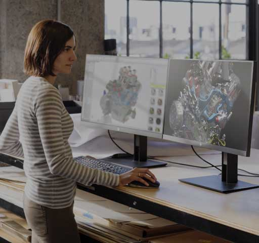 Product Designer standing at her desk with dual monitors using the Z6