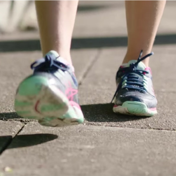 Close up a person's feet walking, wearing sneakers