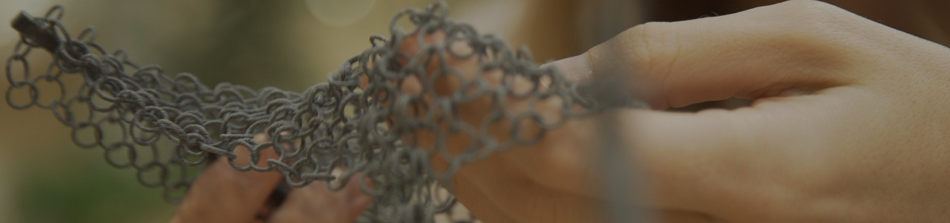 Hands holding 3D printed chain mesh