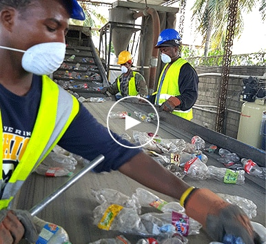 Image of three men separating plastic bottles at recycling facility in Haiti