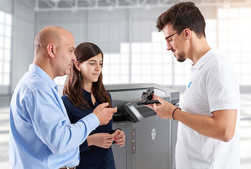 Two women and a man standing in front of an HP Multi Jet Fusion 4200 3D printer looking at 3D printed part
