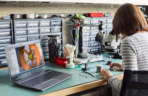 Woman sewing next to HP ZBook 15v