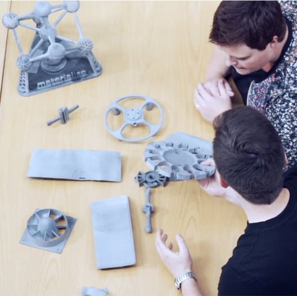 Top view of two men looking at 3D printed parts