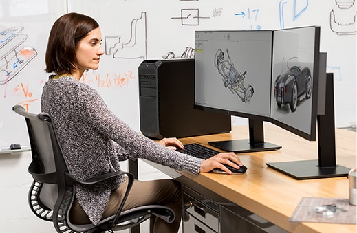 Woman working with HP Z2 Tower workstation in office environment.