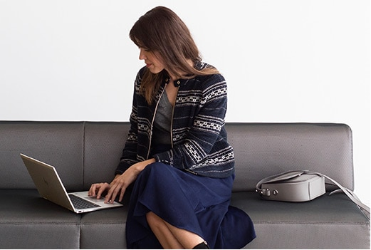Business woman sitting on a couch while using an HP EliteBook x360 business convertible laptop