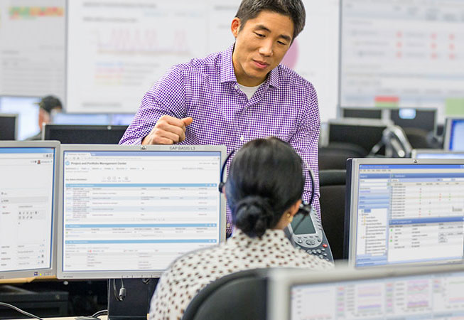 Man speaking to employee in front of working monitors