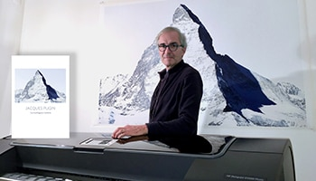 Photographer Jacques Pugin with an HP DesignJet printer and a printed canvas on the wall