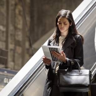 woman using elitebook in tablet mode while on escalator