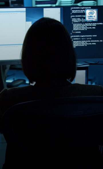 Woman working on hp dual desktop screens entering security code.
