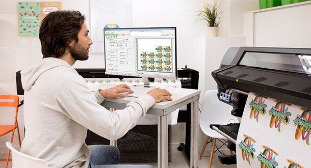 Man using label software on computer and printing labels on HP Latex printer