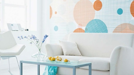 White couch with colorful wallcovering