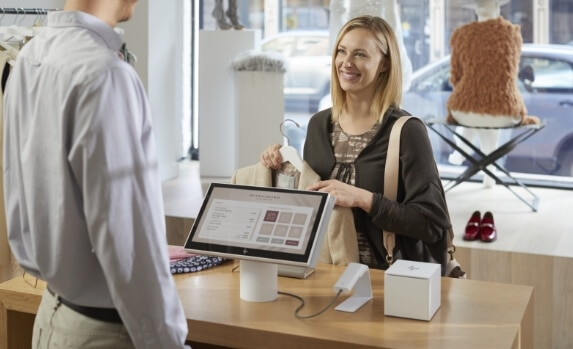 woman talking with sales rep in front of hp retail solutions desktop device