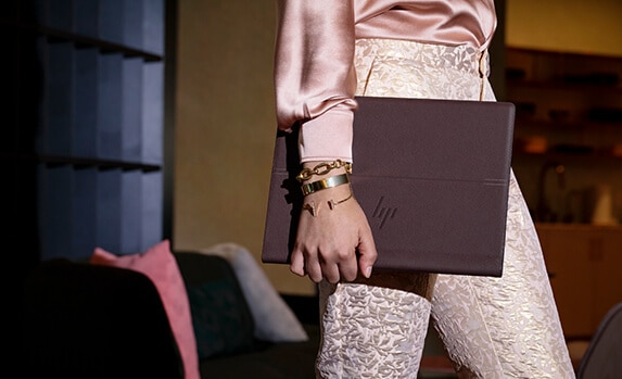 Women with one of HP's Premium notebooks open in front of her while relaxing at home
