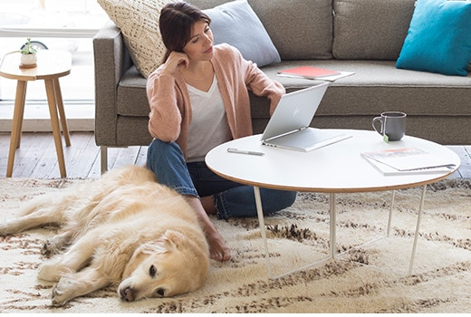 Business woman at home using an HP EliteBook x360 business convertible laptop in media mode