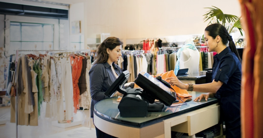 women standing by the counter buying clothes