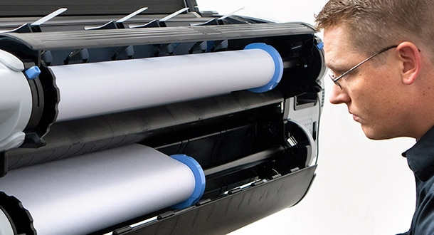 Technician inspecting HP DesignJet printer