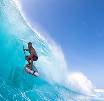 side view of a man surfing on a wave