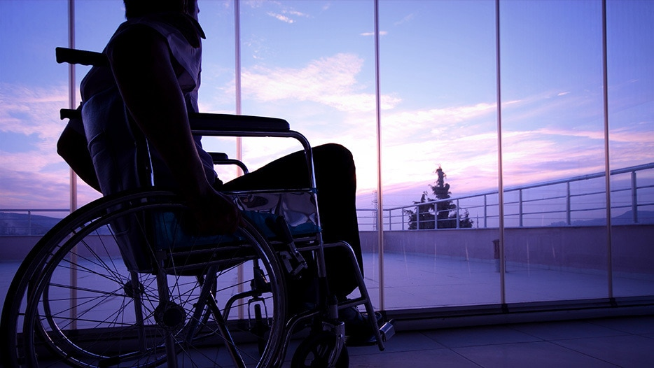 Image of a disabled person on a lobby watching the sundown
