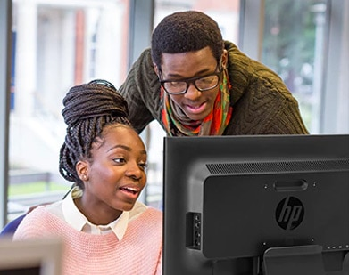 man and woman looking at HP monitor