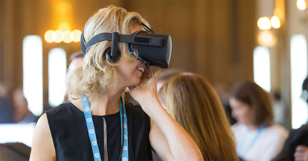 Image of woman with VR headset at Reinvent World Partner Forum 2017