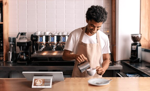 Man pouring milk into a coffee standing next to HP ElitePOS product