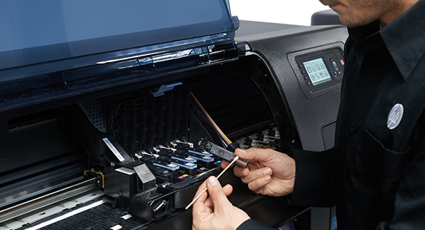 Technician changing ink cartridges into an HP DesignJet printer