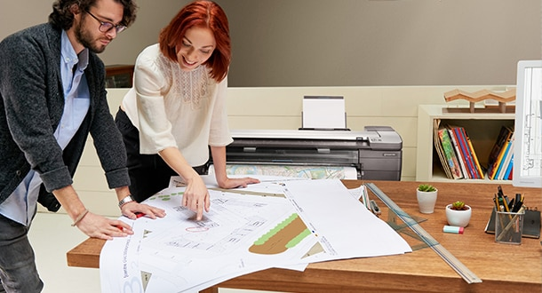 Professionals working with architectural drawing plans printed from an HP DesignJet printer