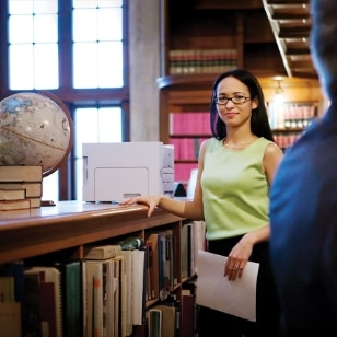 Woman standing next to HP printer in library