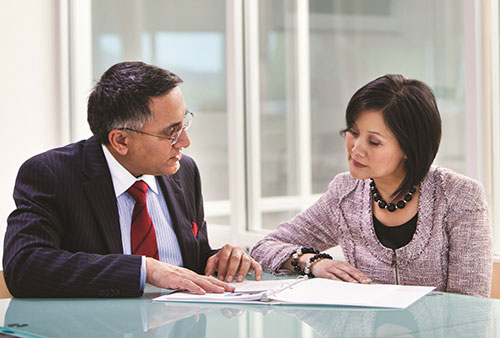 Business man and woman reviewing notebook of information, representing HP Integrated Financial Services