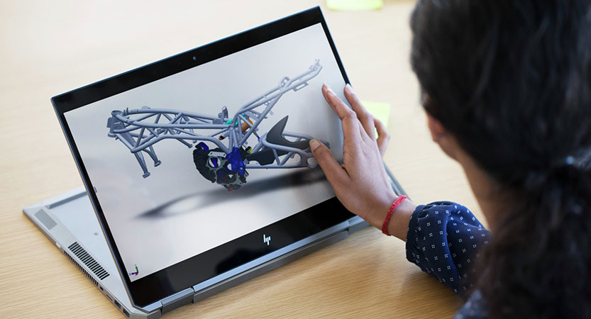 Artist using a finger to edit image on the Zbook studio x360 touch screen