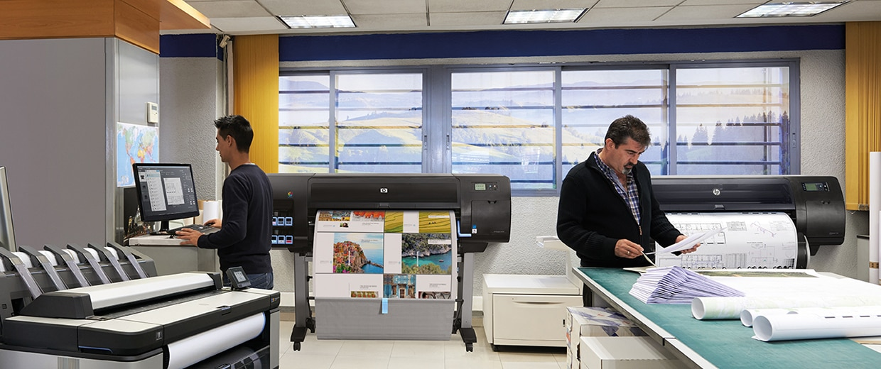 Two men working on HP DesignJet printers, with computer and blueprints