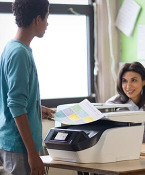 man taking out printed papers from a HP printer and woman in the background